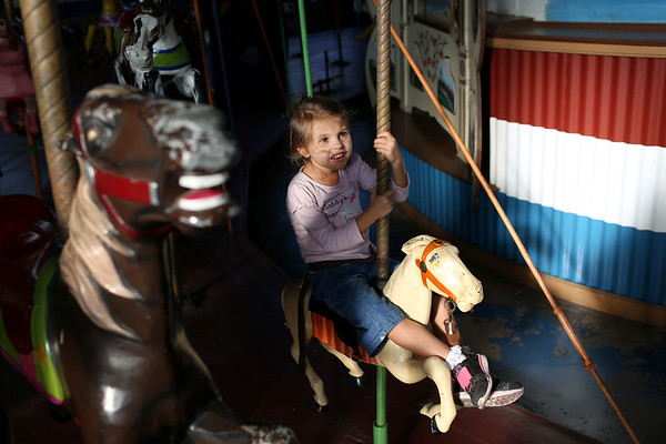 HADLEY GREEN/Staff photo<br /> Laura McKenney rides on the carousel at the Willows park in Salem. She came with her father, Cliff McKenney, who has been coming to the Willows for over forty years. <br /> <br /> 08/31/17