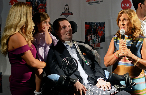 "RYAN HUTTON/ Staff photo<br /> Beverly native and ALS sufferer Pete Frates, center, is surrounded by wife Julie and daughter Lucy, 3, left and mother Nancy, right, in the State Street Pavilion at Fenway Park on Monday night for an event to support the book about him ""The Ice Bucket Challenge"" - a chronicle of his struggles with ALS and how he helped start the famed ice bucket challenge to raise money for ALS research."