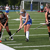 HADLEY GREEN/Staff photo<br /> Bishop Fenwick's Kat Clancy (7) and Courtney Muir (4) vie for the ball while Danvers' Mackenzie Schmink (10) plays defense at the Danvers v. Bishop Fenwick girls field hockey game at Danvers High School.<br /> 09/21/17