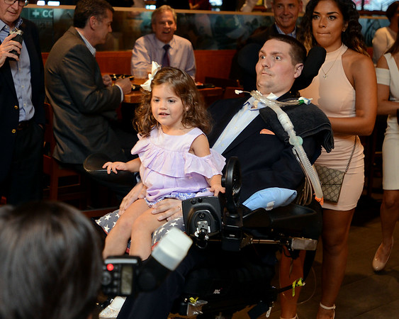 """RYAN HUTTON/ Staff photo<br /> Beverly native and ALS sufferer Pete Frates enters the State Street Pavilion at Fenway Park on Monday night with his daughter Lucy, 3, in his lap for an event to support the book about him """"The Ice Bucket Challenge"""" - a chronicle of his struggles with ALS and how he helped start the famed ice bucket challenge to raise money for ALS research."""