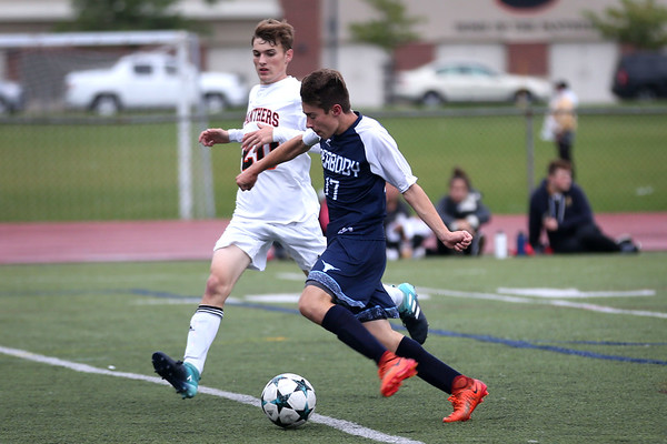 HADLEY GREEN/Staff photo<br /> Peabody's Jonathan Alves (17) prepares to shoot and score while Beverly's Ben Sarcione (20) defends him at the Beverly v. Peabody boys varsity soccer game at Beverly High School.<br /> 09/20/17