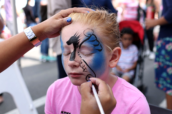 HADLEY GREEN/Staff photo<br /> Jessica Saunders, 10, of Peabody, has her face painted by  Giovanna Forsley at the International Festival in Peabody.<br /> 09/10/17