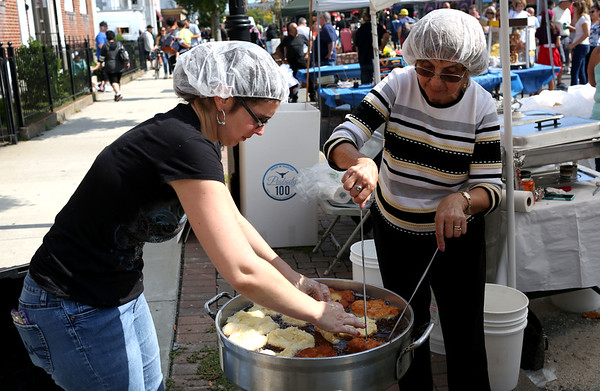 HADLEY GREEN/Staff photo<br /> Sandy Cunha, left, and Fernanda Sioveira, right, make friend dough at the tent for the Holy Ghost Society of Peabody at the International Festival.<br /> 09/10/17