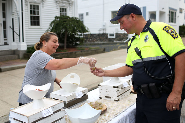 HADLEY GREEN/Staff photo<br /> Lisa Lotruglio of Bella & Harvey hands Peabody police officer Brian Colella a sample of her homemade salsa at Peabody's block party on Chestnut Street next to City Hall. <br /> 09/08/17