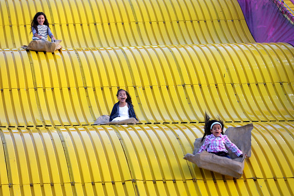 HADLEY GREEN/Staff photo<br /> Adryanna Figueiredo, 7, Angelis Espillat, 6, and Mia Sofia Feliz, 6, all of Salem, fly down the giant slide at the Topsfield Fair.<br /> 09/29/17