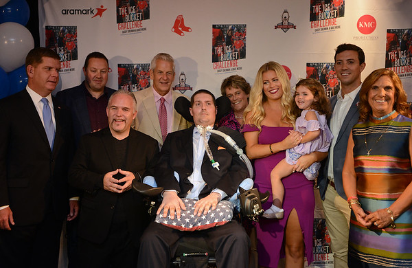 """RYAN HUTTON/ Staff photo<br /> Beverly native and ALS sufferer Pete Frates, center, is surrounded by Boston Mayor Marty Walsh, far left, authors Casey Sherman and Dave Wedge left, his wife Julie and daughter Lucy, 3, right brother Andy and mother Nancy, far right, at the State Street Pavilion at Fenway Park on Monday night for an event to support the book about him """"The Ice Bucket Challenge"""" - a chronicle of his struggles with ALS and how he helped start the famed ice bucket challenge to raise money for ALS research."""