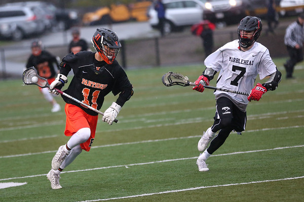 HADLEY GREEN/ Staff photo<br /> Beverly's Dakota Lillelund (11) moves the ball up the field while Marblehead's Joe Cronin (7) defends him at the Marblehead v. Beverly boys varsity lacrosse game held at Marblehead High School on Tuesday, April 25th, 2017.