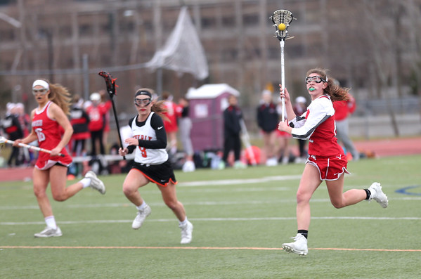 HADLEY GREEN/ Staff photo<br /> Masco's Jordyn Tveter (15) runs towards the goal while Beverly's Sabrina Beaudry (8) guards her on the left during the Masco v. Beverly girls varsity lacrosse game at Beverly High on Friday, April 7th, 2017.
