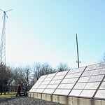 HADLEY GREEN/ Staff photo People walk by a windmill and solar panels at the  Greenergy Park Solar Field.
