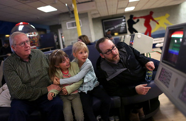 HADLEY GREEN/ Staff photo<br /> From left to right, Don Mahnke, his grandchildren Beatrice and Juniper, and son Aaron Mahnke check the game score while bowling at Sunnyside Bowladrome in Danvers on Friday, April 21st, 2017.