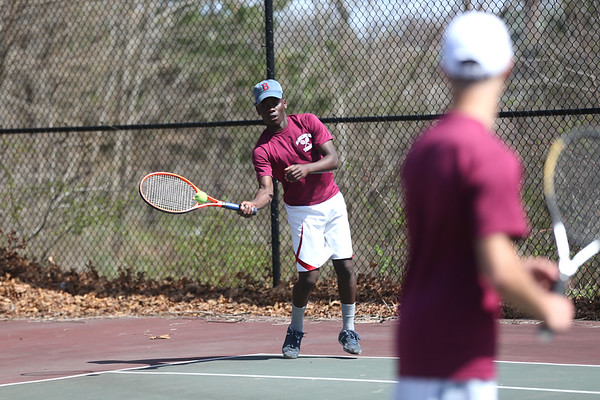 HADLEY GREEN/ Staff photo<br /> Gloucester's Joe Kibango hits the ball while playing doubles with teammate Anthony Parco at the Marblehead v. Gloucester boys tennis match at Marblehead High School on Monday,  April 17th, 2017.