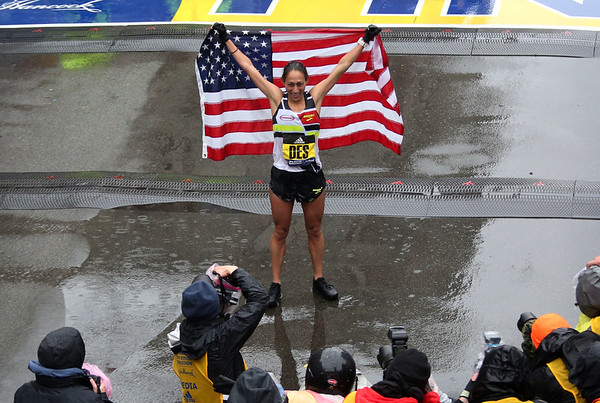 HADLEY GREEN/Staff photo<br /> Women's winner Desiree Linden of Michigan holds the American flag at the finish line of the 122nd Boston Marathon.<br /> <br /> 04/16/18