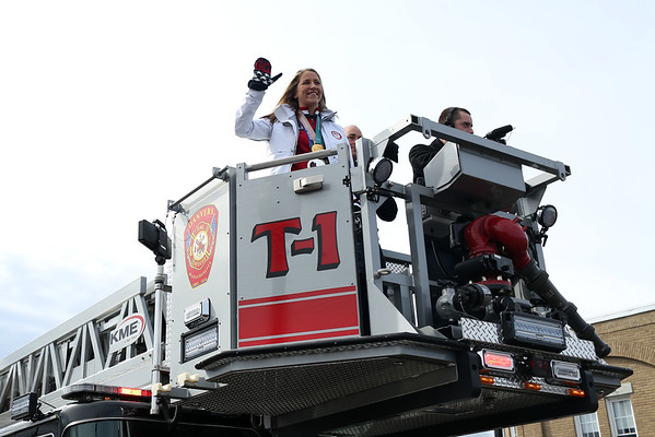 HADLEY GREEN/Staff photo<br /> Meghan Duggan rides in a Danvers fire truck to greet Danvers residents for the Meghan Duggan Day celebration.<br /> <br /> 04/07/18