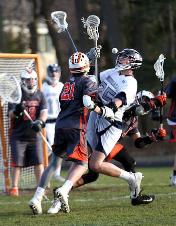 HADLEY GREEN/Staff photo<br /> Hamilton-Wenham's Griffin Barlow (25) shoots while Ipswich's Jack Sotiropoulos (21) plays defense at the Hamilton-Wenham v. Ipswich boys lacrosse game.<br /> <br /> 04/24/18