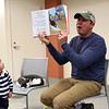"HADLEY GREEN/Staff photo<br /> Lochlin Garcia-Dale, 2, of Ipswich, listens while Jonathan Hall, author of ""Toto the Tornado Kitten,"" reads aloud his book at the Ipswich Public Library. Toto the cat sleeps in a seat next to him. <br /> <br /> 04/18/18"