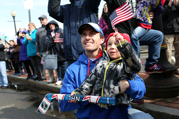HADLEY GREEN/Staff photo<br /> Chris Soucy and his son William greet Meghan Duggan as she rides in a fire truck through Danvers center. <br /> <br /> 04/07/18