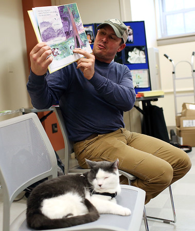 """HADLEY GREEN/Staff photo<br /> Jonathan Hall, author of """"Toto the Tornado Kitten,"""" reads aloud his book at the Ipswich Public Library. Toto, Hall's adopted cat, sits in a seat next to him. <br /> <br /> 04/18/18"""