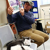 "HADLEY GREEN/Staff photo<br /> Jonathan Hall, author of ""Toto the Tornado Kitten,"" reads aloud his book at the Ipswich Public Library. Toto, Hall's adopted cat, sits in a seat next to him. <br /> <br /> 04/18/18"