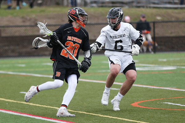 HADLEY GREEN/Staff photo<br /> Beverly's Rawding (20) moves the ball while Marblehead's Mason Polson (6) plays defense at the Marblehead v. Beverly boys lacrosse game at Marblehead High School.<br /> <br /> 04/19/18