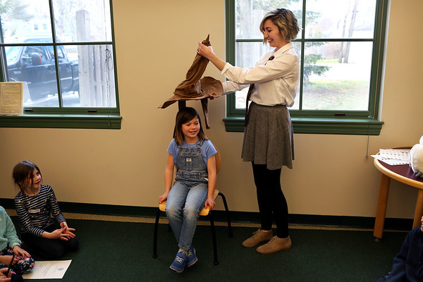 """HADLEY GREEN/Staff photo<br /> Grace Logemann, 8, of Wenham, takes her turn with the """"sorting hat"""" at the Harry Potter event at the Hamilton-Wenham Public Library.<br /> <br /> 04/17/18"""