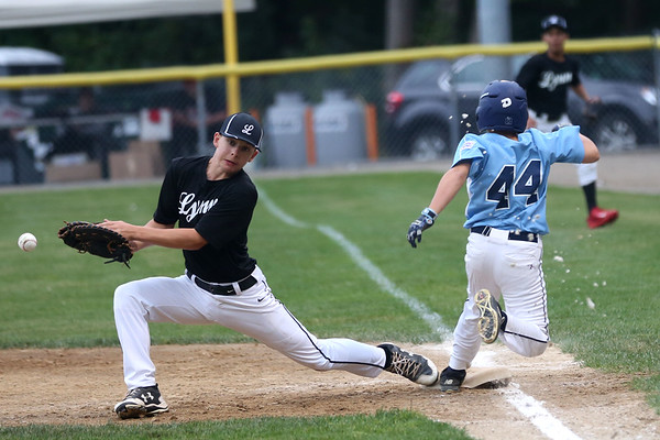 HADLEY GREEN/Staff photo<br /> Lynn's Jack Marks (8) lunges to catch the ball while Peabody's Daniel Zizza (44) sprints to first base at the Peabody v. Lynn Gallant baseball championship game at the Harry Ball Field in Beverly. 8/15/17