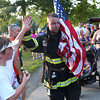 HADLEY GREEN/Staff photo<br /> Beverly firefighter Andrew Bencal high-fives Gabin Ferretti of Beverly after crossing the finish line at the Beverly Homecoming Road Race at Lynch Park. 8/03/17