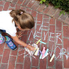 "HADLEY GREEN/Staff photo<br /> Emma Anderson of Beverly draws a heart next to a chalk message that reads ""Hate never works"" on Beverly Common at the Rally for Love. 8/18/17"