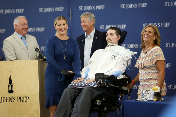 HADLEY GREEN/Staff photo<br /> Pete Frates, his wife Julie Frates, mother Nancy Frates, and father John Frates, stand with St. John Prep's athletic director and Pete's former football coach, Jim O'Leary. St. John's Prep honored Pete Frates with the 2018 Distinguished Alumnus Award, retired his number three jersey, and dedicated a baseball field to him, the Pete Frates '03 Diamond. 08/30/17