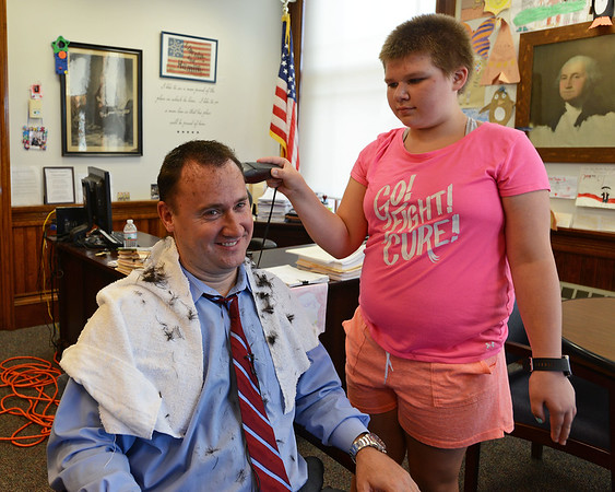 RYAN HUTTON/ Staff photo<br /> Alaina Hutchinson, 12, buzzes the hair off of Peabody Mayor Ted Bettencourt in his office on Wednesday to fulfill a promise Bettencourt made to the Higgins Middle School seventh grader when she cut off all her hair in June to support kids with cancer.