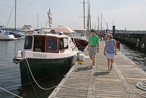 """MIKE SPRINGER/Staff photo<br /> Joe and Debra D'Arcy of Amesbury look at the Nomad, a """"micro trawler"""" owned by Michael Schiller of Hull, during the annual Antique and Classic Boat Festival on Saturday in Salem.<br /> 8/25/18"""
