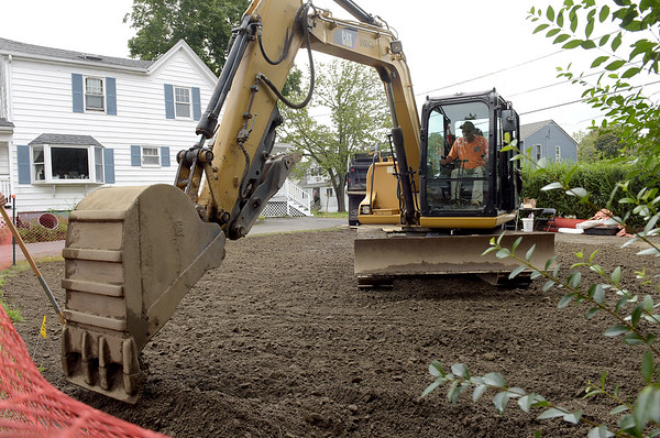 TIM JEAN/Staff photo<br /> <br /> A workers from Environmental Restoration LLC., a contractor for the EPA spreads clean topsoil to a yard on Fowler Street in Danvers. The EPA has been removing arsenic contaminated soil from the Brown Pond area for weeks, and hope to be finished this fall.   8/22/18
