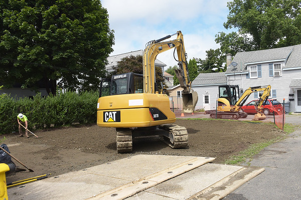 TIM JEAN/Staff photo<br /> <br /> A workers from Environmental Restoration LLC., a contractor for the EPA rakes clean topsoil in a yard on Fowler Street in Danvers. The EPA has been removing arsenic contaminated soil from the Brown Pond area for weeks, and hope to be finished this fall.   8/22/18