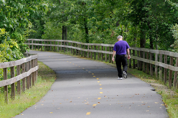 TIM JEAN/Staff photo<br /> <br /> A walker on a section of the Peabody Independence Greenway. The city has received a grant to move forward with a project to expand the trail to the downtown.   8/22/18