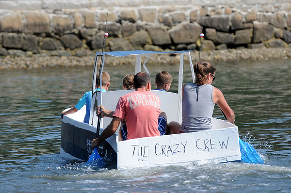 PAUL BILODEAU/Staff photo. The Crazy Crew, Anthony Gaglione, left, his wife, Cait and their two kids Ben and Ryan along with a family friend, Emily Gustofson, head to the finish line during the annual Beverly Home Coming Cardboard Boat Race at Lynch Park in Beverly.  8/5/18