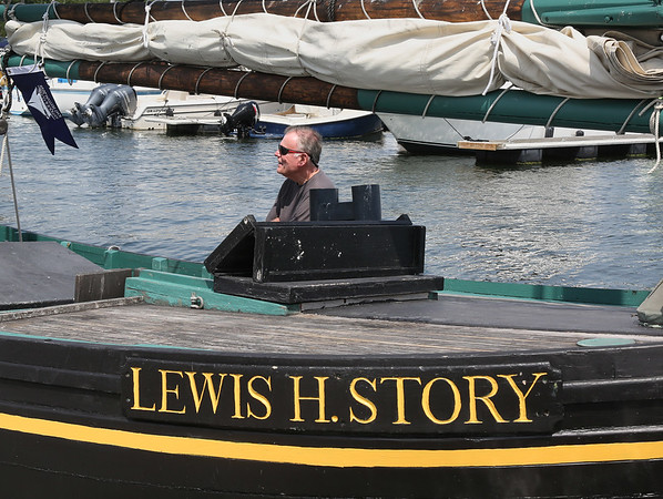 MIKE SPRINGER/Staff photo<br /> Bob Guadros of the Essex Shipbuilding Museum sits aboard the Lewis H. Story, a 38-foot Chebacco boat designed and built by Harold Burnham of Essex, during the annual Antique and Classic Boat Festival on Saturday in Salem.<br /> 8/25/18
