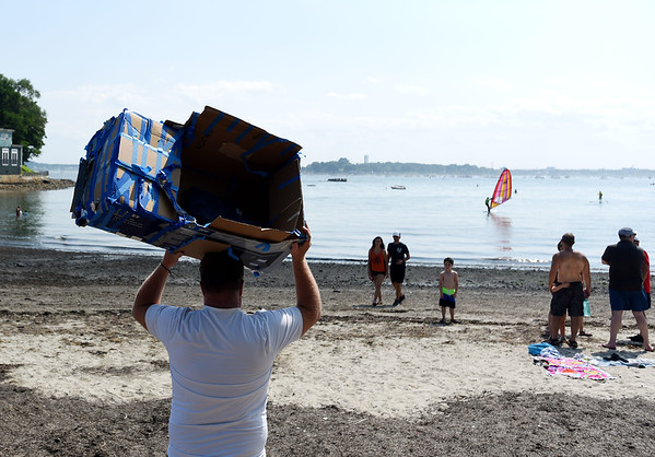 PAUL BILODEAU/Staff photo. John Irons, left, carries his son Steele's cardboard boat to the water before the start of the annual Beverly Home Coming Cardboard Boat Race at Lynch Park in Beverly.  8/5/18