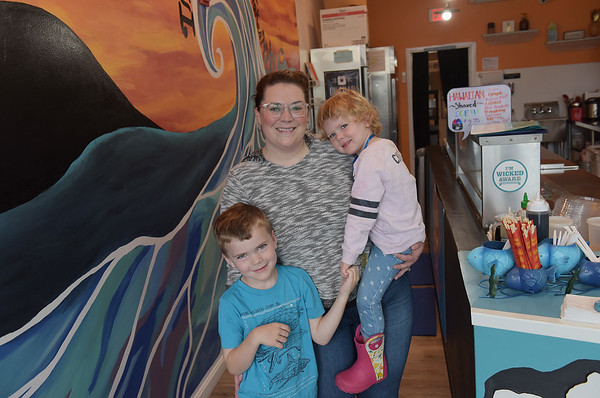 TIM JEAN/Staff photo<br /> <br /> Kristen Hollingsworth, owner of Lolo Poke, with her children Ryan, 6, and Ava, 3, pose in front of a mural painted by the art students at Beverly High School. The new restaurant on Rantoul Street in Beverly, offers Hawaiian cuisine.    8/22/18