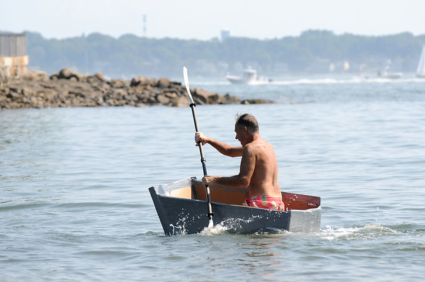 PAUL BILODEAU/Staff photo. Stephen Fall of Beverly races to the finish line in his cardboard boat during the annual Beverly Home Coming Cardboard Boat Race at Lynch Park in Beverly.  8/5/18