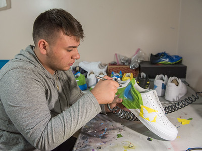 AMANDA SABGA/Staff photo  Recent high school graduate Vinnie Ducharme, 18, of Groveland airbrushes a butterfly design onto a pair of sneakers. Ducharme is building his name and brand by custom designing sneakers as Late Night Custom.   8/13/19
