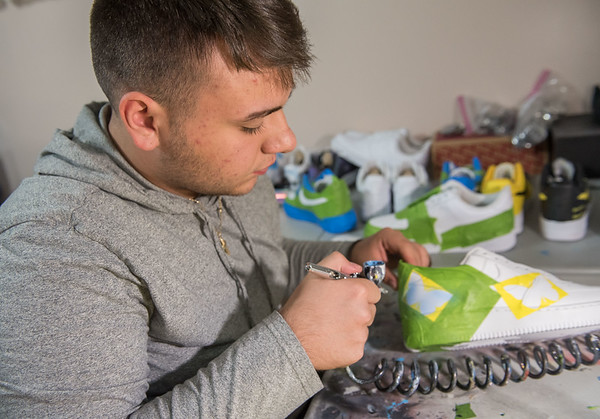 AMANDA SABGA/Staff photo<br /> <br /> Recent high school graduate Vinnie Ducharme, 18, of Groveland airbrushes a butterfly design onto a pair of sneakers. Ducharme is building his name and brand by custom designing sneakers as Late Night Custom. <br /> <br /> 8/13/19