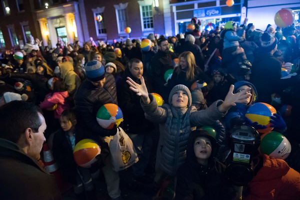 The crowd waits for more beach balls to be dropped from above during Beverly's New Year's celebration on Cabot Street. 12/30/16