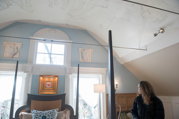 SAM GORESH/Staff photo. Kristin Mielcarz admires the bedroom decorated with artwork made by homeowner artist Thomas Darsney during the Christmas in Salem House Tour. 12/4/16
