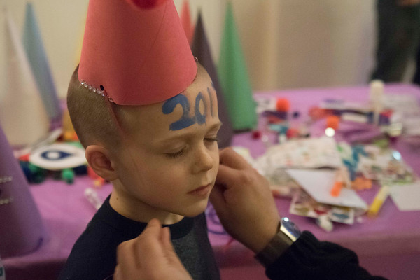 SAM GORESH/Staff photo. Jack Bedner, 5, waits patiently as volunteer ties the hat that Bedner decorated at Salem Main Streets' Launch New Year's Eve event for families at the Old Town Hall. 12/31/16