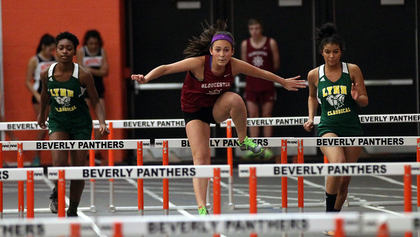 DAVID LE/Staff photo. Gloucester junior Kaitlin Marques flies over a hurdle en route to a win in the 55m high hurdles against Lynn Classical on Tuesday afternoon. 12/20/16