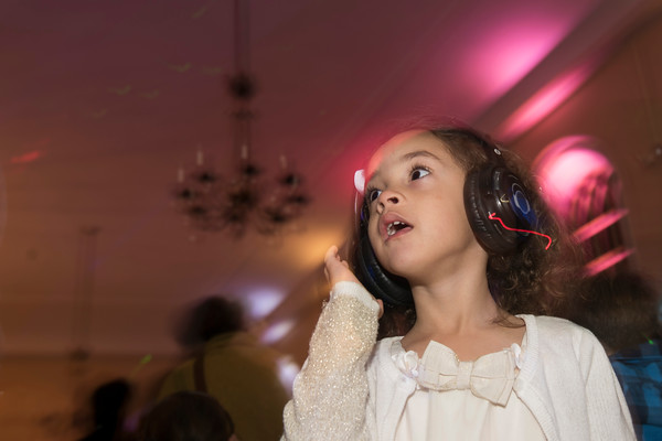 SAM GORESH/Staff photo. Amelia Harewood, 3, pauses as a new song comes on her headphones at the silent disco at the Salem Main Streets' Launch New Year's Eve event for families at the Old Town Hall. 12/31/16