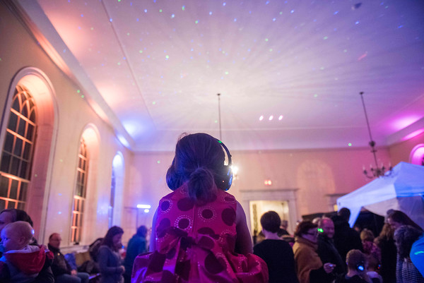 SAM GORESH/Staff photo. Olivia Reale, 6, sits on her father George Reale's shoulders at the silent disco during the Salem Main Streets' Launch New Year's Eve event for families at the Old Town Hall. 12/31/16