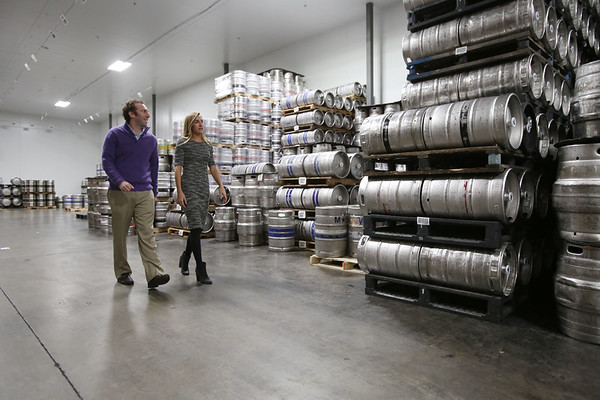 Ken Yuszkus/Staff photo  Mark and Jennifer Tatelman walk along the kegs of beer stored in the refrigerated area of the Merrimack Valley Distributors warehouse.       12/7/17