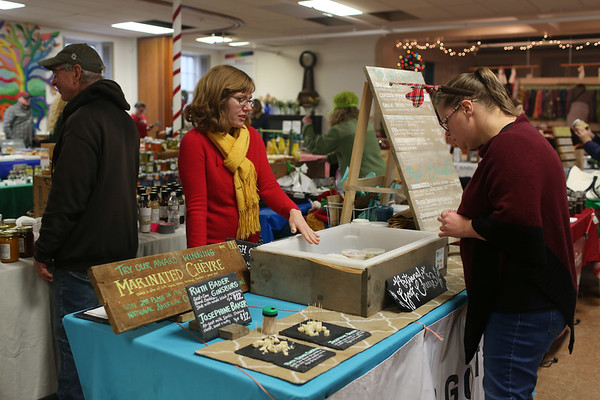HADLEY GREEN/Staff photo<br /> A shopper looks at cheese at the Dancing Goats Dairy table at the Cape Ann Farmer's Market at the Unitarian Universalist Church in Gloucester.<br /> <br /> 12/23/17