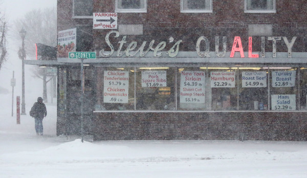 HADLEY GREEN/ Staff photo<br /> A man stands outside Steve's Quality Market in Salem during Thursday's snowstorm.