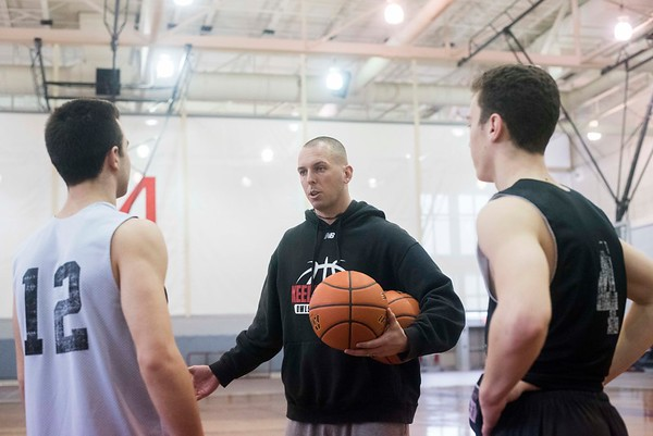 SAM GORESH/Staff photo. Marblehead assistant coach Chris Timson talks to seniors Justin Feia (left) and Drew Gally (right) during their practice at Marblehead High School. 2/12/17